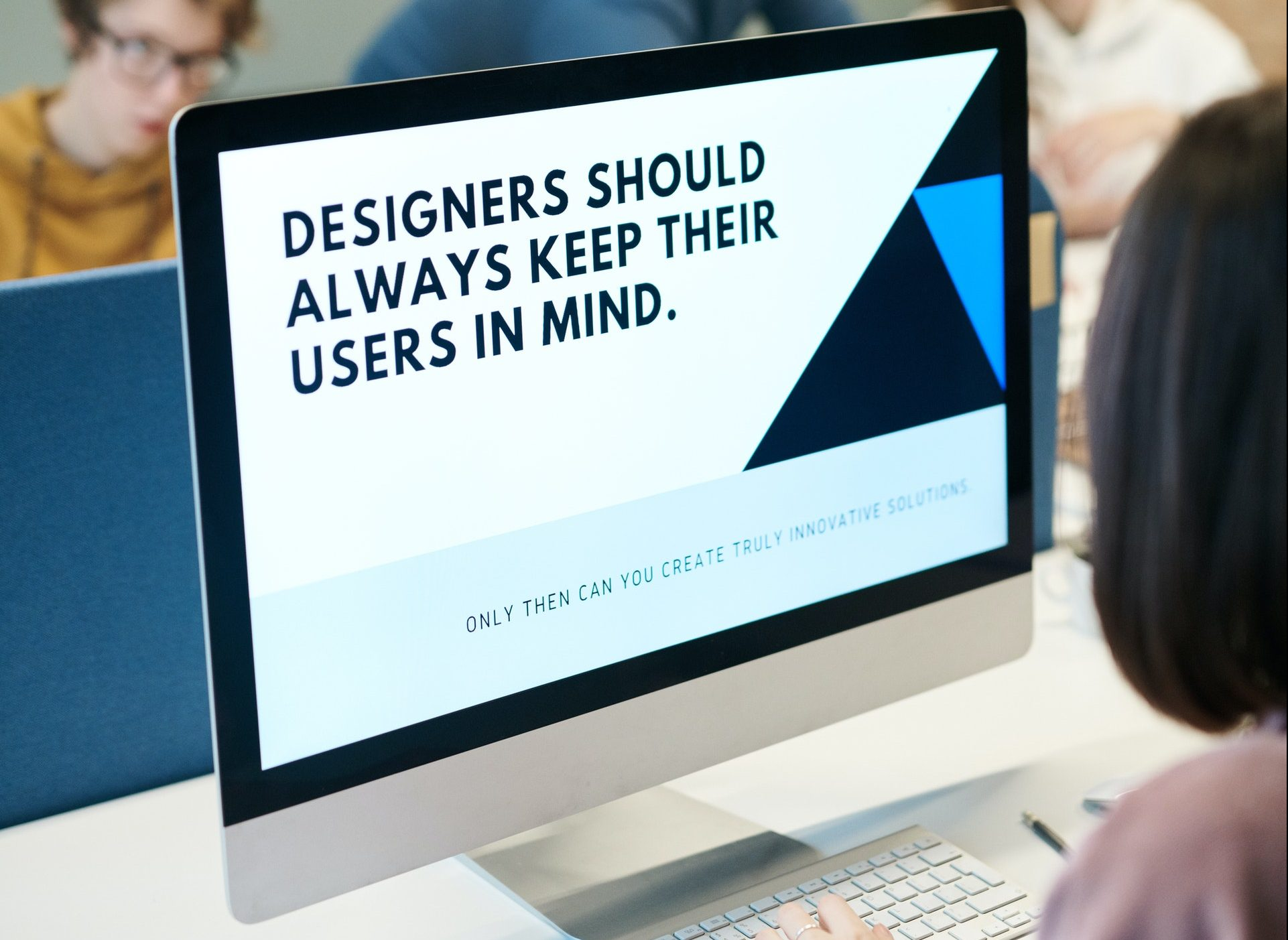 "computer monitor with presentation slide that says ""Designers should always keep their users in mind""."